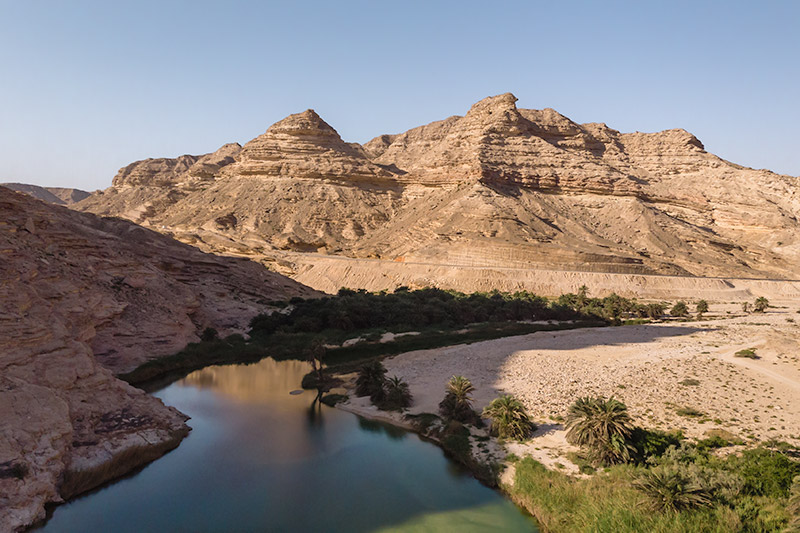 An aerial view over the green water of Wadi Suneik, mountains towering in the background