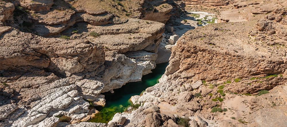 An emerald green pool below dry orange cliffs at Wadi Uyun north of Salalah