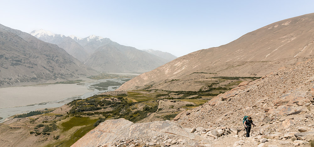 A woman with a backpack hikes up a rocky trail with a view of the Wakhan Valley behind her