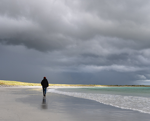 A person walking beneath dark stormy clouds on Sanday, one of the Orkney Islands