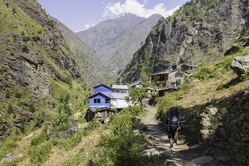 A hiker walks along the sunny trail towards a small village in the sun