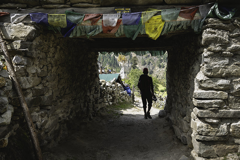 A person walking through the short tunnel of a stone gate on the Manaslu Circuit Trek