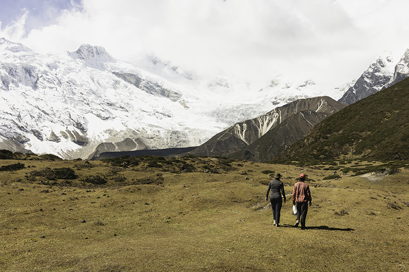 With snow covered Mt. Manaslu in the distance, two people walk across the high pasture towards Pungen Gompa