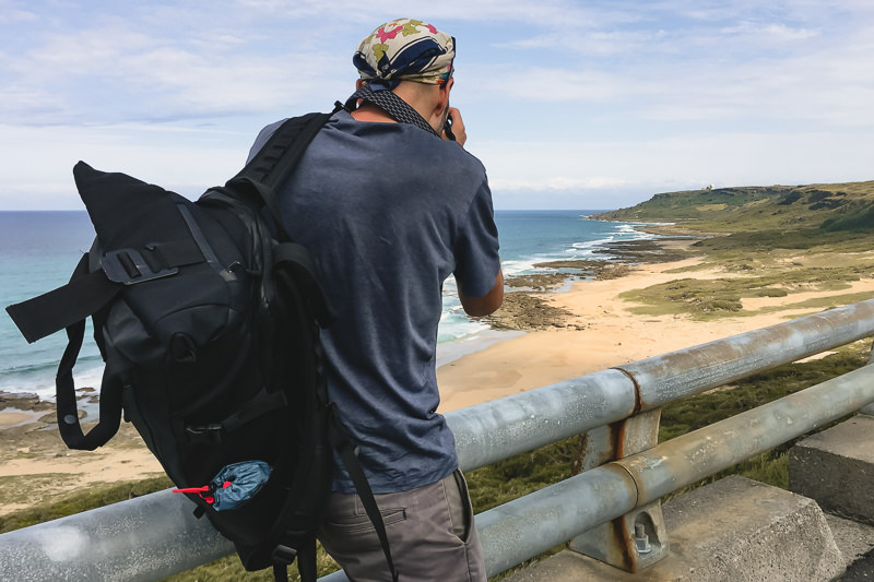 A photographer with the Wandrd Prvke 31 slung over one shoulder takes a picture of the coast in Kenting National Park, Taiwan
