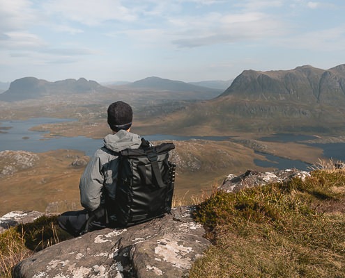 A hiker wearing the Wandrd Prvke travel camera bag looks out from Stac Pollaidh towards Suilven in the Scottish Highlands