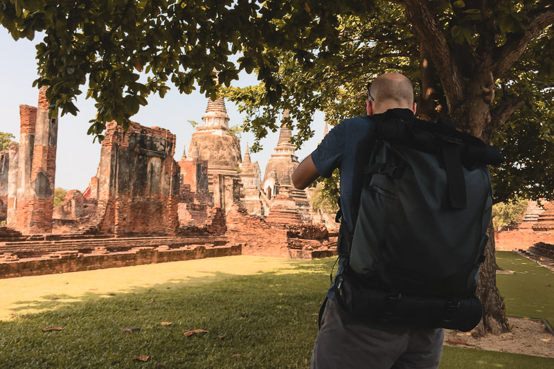 A photographer taking a shot while wearing the Wandrd Prvke 31 at Ayutthaya in Thailand