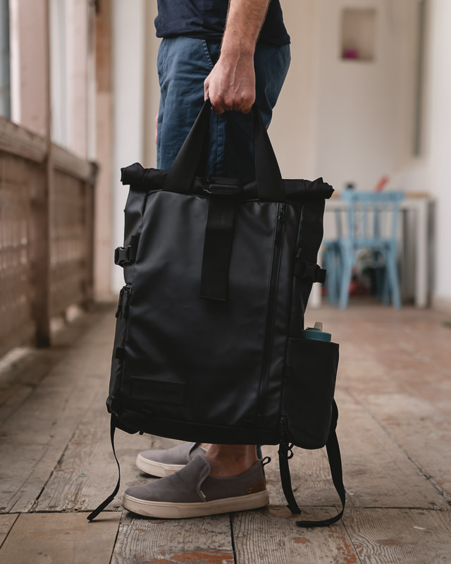 A person holding the Wandrd Prvke 31 travel camera bag using the magnetic carry handles.