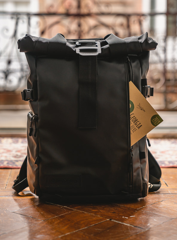 A frontal view of the Wandrd Prvke 31 travel camera bag showing a slim book in the opening of the wide front pocket.