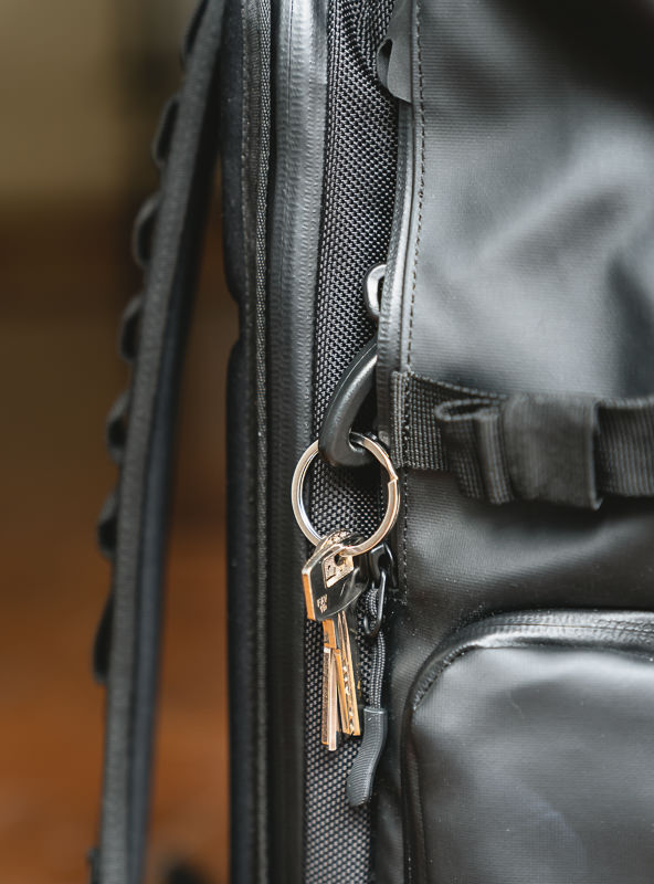 A close up of the Wandrd Prvke 31 key pocket at the side of the bag, with keys dangling from the attached key chain.