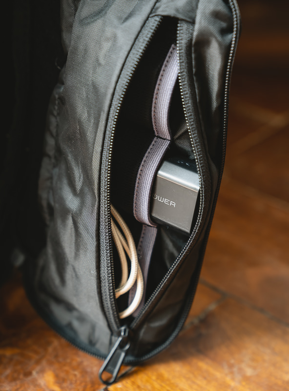 Wandrd Prvke camera bag side mesh pockets with camera batteries and USB cable showing