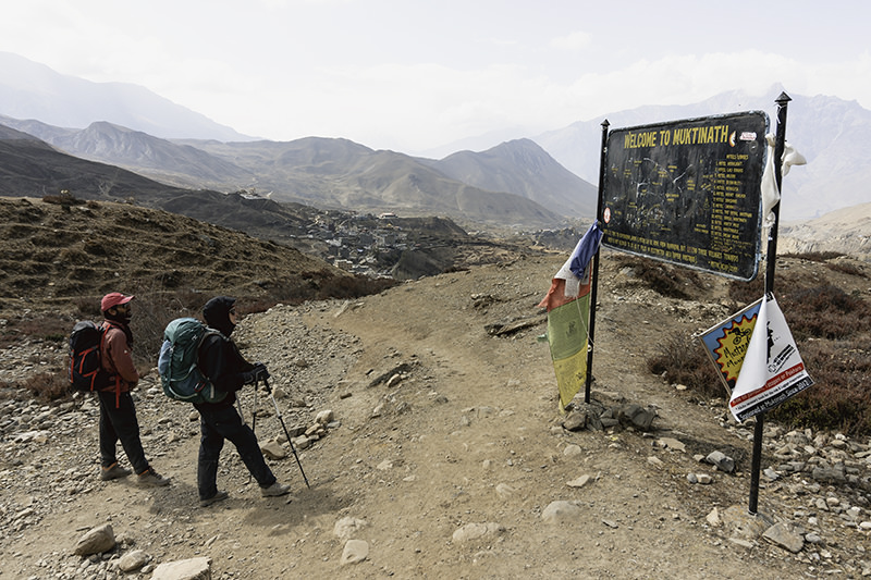 Two trekkers looking at a hand painted metal sign with a map of Muktinath