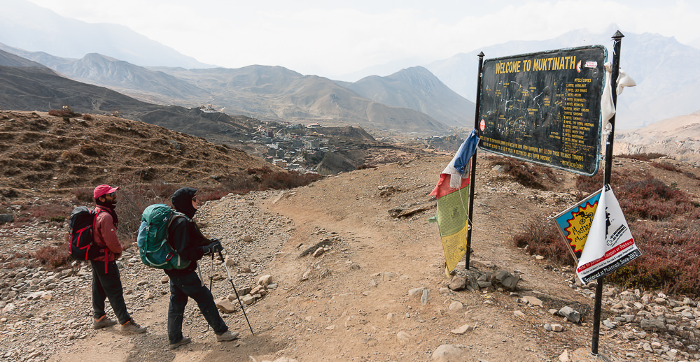 wo trekkers looking at a hand painted metal sign with a map of Muktinath