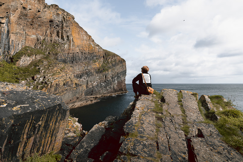 A person sits looking up at the rocky cliffs at Whaligoe Haven, a stunning natural harbour that can be seen on the North Coast 500 route in Scotland.
