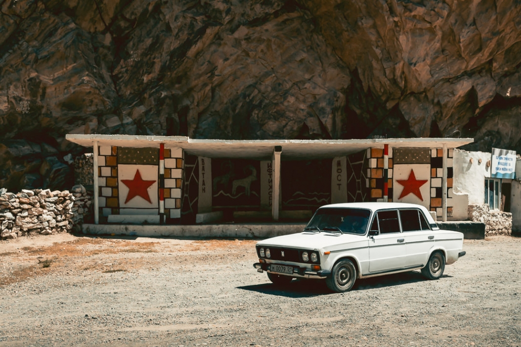 A Lada pulls up in front of a particularly eye catching Soviet bus stop on the Pamir Highway in Tajikistan