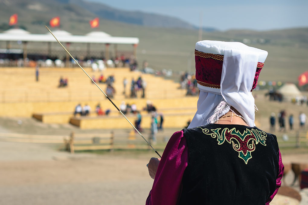 This woman, dressed in an elaborate embroidered outfit at the World Nomad Games in Kyrgyzstan, is expertly wrapping wool around the thin bamboo cane, to be used as part of the pattern in one of the traditional decorative mats.