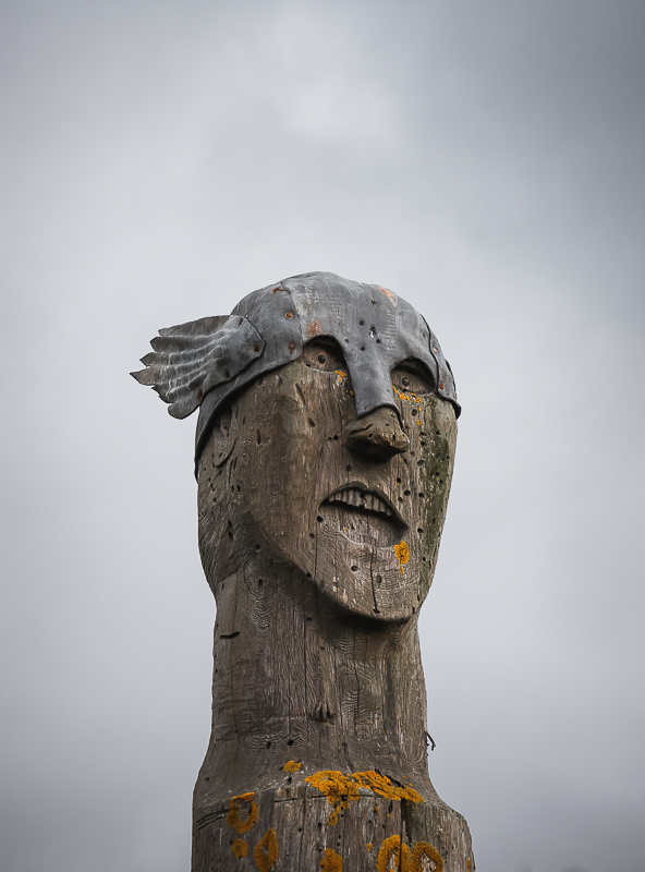 The head of a carved wooden viking statue on a beach in the Orkney Islands