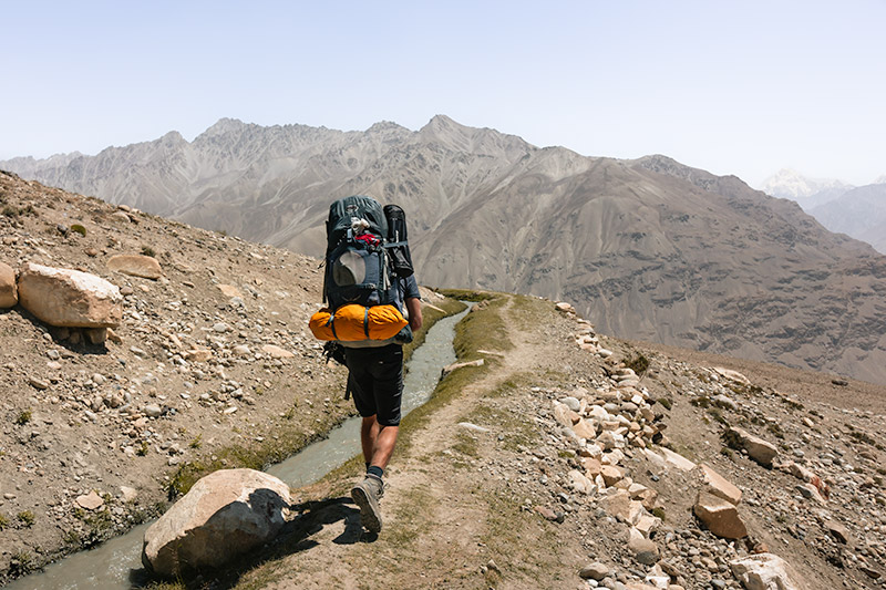 A person with big backpack and tent walks on a narrow trail looking out to the Wakhan Valley below