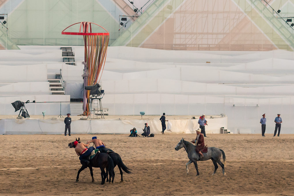 Horseback wrestling, known as Er Enish, is one of the main sporting events at the World Nomad Games. The aim is to pull your opponent from his horse using a series of dangerous holds. It's a sport in which the horse's strength and skill is just as important as the wrestler's. Two barechested riders tussle while the referee looks on.