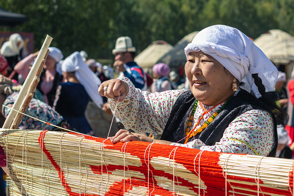A woman adds a piece of bamboo cane to the mat. Each cane has already been individually wrapped according to the design, so each has an exact place it must go. The dangling strings are held weighed down by small rocks; as each cane is slid in, the strings are moved to the opposite side, crossing each other to bind the cane to the mat. One of many traditional skills on show at the World Nomad Games in Kyrgyzstan.