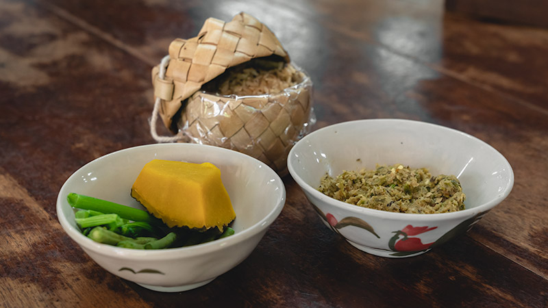 A bowl of Nam Prik, a Lanna Cuisine paste, accompanied by a bowl of steamed veg and a basket of sticky rice.