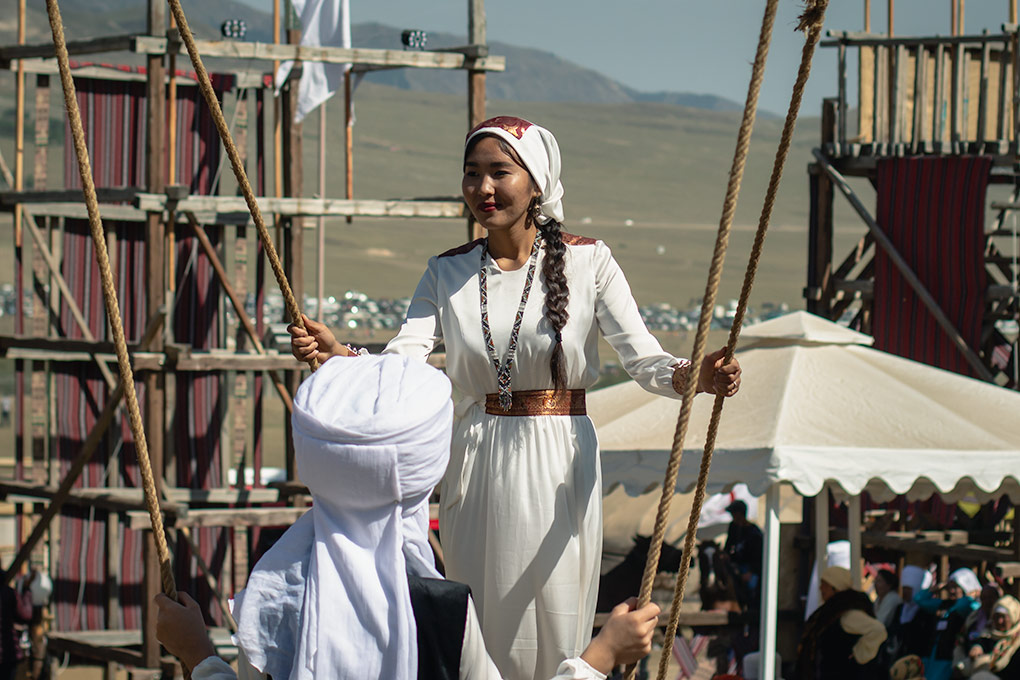 Hanging out on a traditional swing at the World Nomad Games in Kyrgyzstan, these two young ladies were an instant draw for anyone with a camera. Dressed in traditional clothing, they are standing at either end holding onto two diagonal ropes that hold the swing. Very sedate and calm.