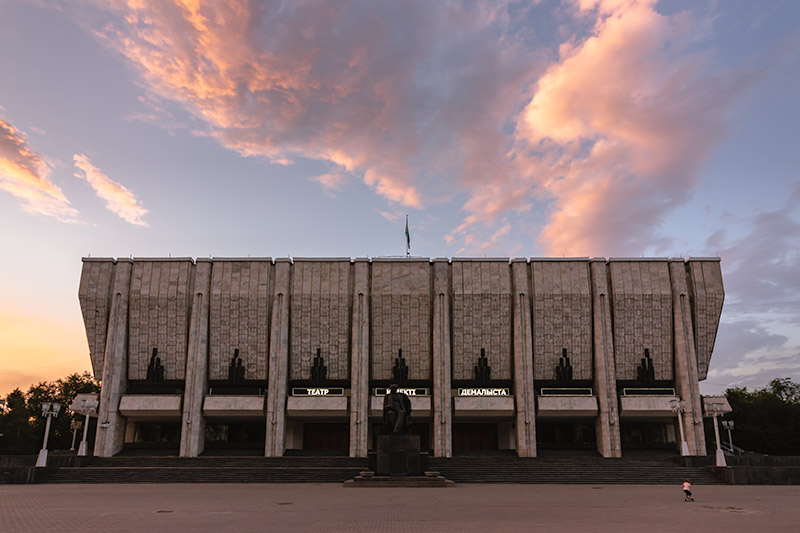 Auezov Theatre (Kazakh State Academic Drama Theatre). The theatre, seen here under pink hued skies at sunset is a fine example of Soviet-era art and architecture in Almaty.