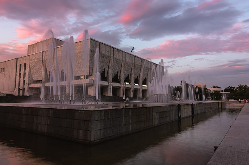 Auezov Theatre (Kazakh State Academic Drama Theatre). The block-like building and surrounding fountains are tinged pink by the sunset hues.