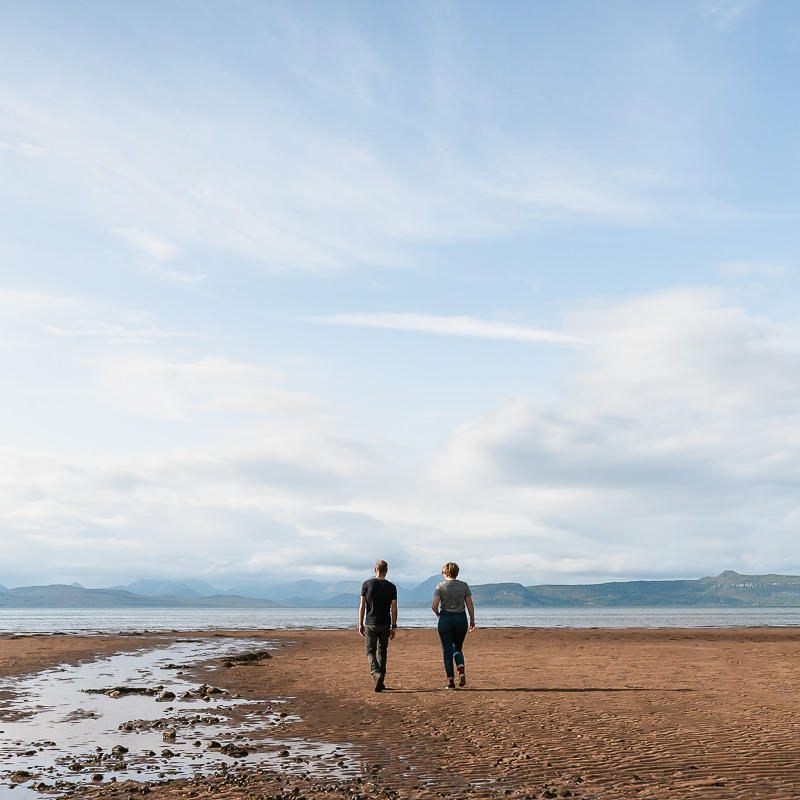 Kim and Del Hogg walk towards the shore on a sandy Scottish beach under light blue skies and whispy white clouds