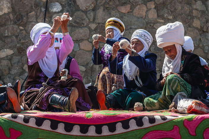In their element, these venerable ladies at the World Nomad Games in Kyrgyzstan are showing off their skills by expertly spinning yarn. Dressed in traditional clothes and wearing elaborate hats and scarves, they are sitting on a colourful rug in the sun.