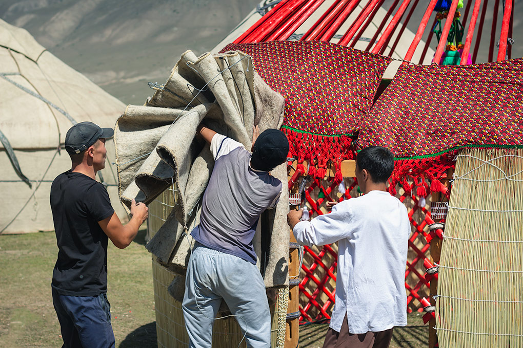 A fascinating display of yurt assembly at the World Nomad Games in Kyrgyzstan. Three men rush to get the roof covering on the red painted frame of the yurt. The aim of the contest was to put together the yurt - from scratch - in the fastest possible time. Judges would measure not just time but that they were all correctly assembled.